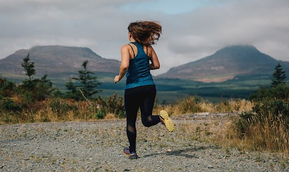 Woman running overlooking mountains