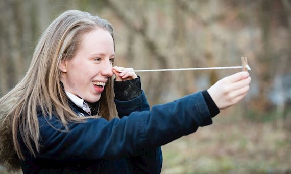 Girl using string and peg to measure tree height