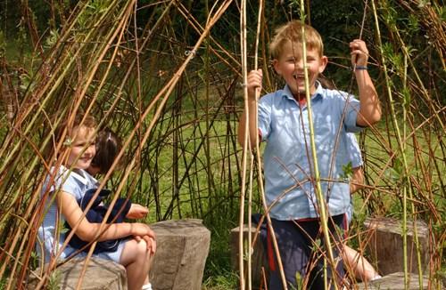 Children playing in school grounds willow dome Ysgol Cynddelw. Glyn Ceiriog. Wrexham