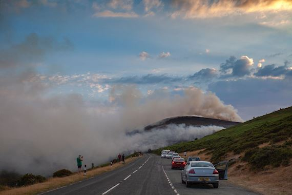 Public spectators watching the moorland fire at Llantysilio Mountain along the Horseshoe Pass, Corwen near Llangollen as the fire burns over the mountain due to heatwave temperatures in the UK