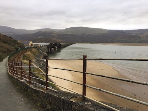An image of the Mawddach estuary with the railway bridge across from Barmouth to Fairbourne. The image shows how closely the train tracks are to the edge of the coastline in this area