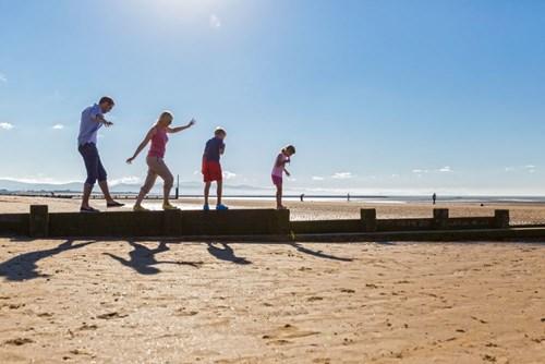 Family walking along groyne on Rhyl beach