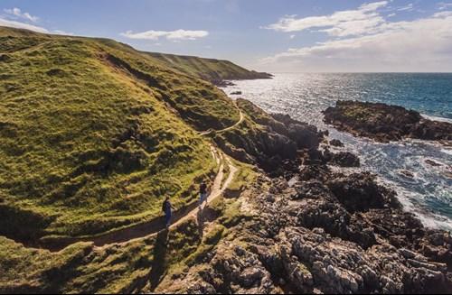 A Pair Of Walkers On The Wales Coastal Path At Porthor, Llŷn Peninsula Where Rugged Green Hills Meet The Sea