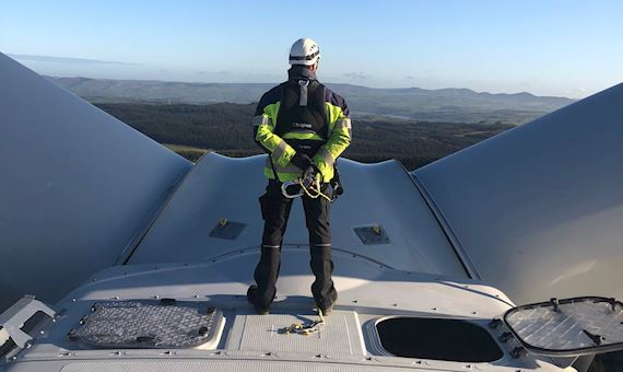 Turbine engineer standing on top of wind turbine looking out at Welsh landscape