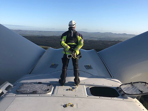 Turbine engineer standing on top of a wind turbine looking out at Welsh landscape