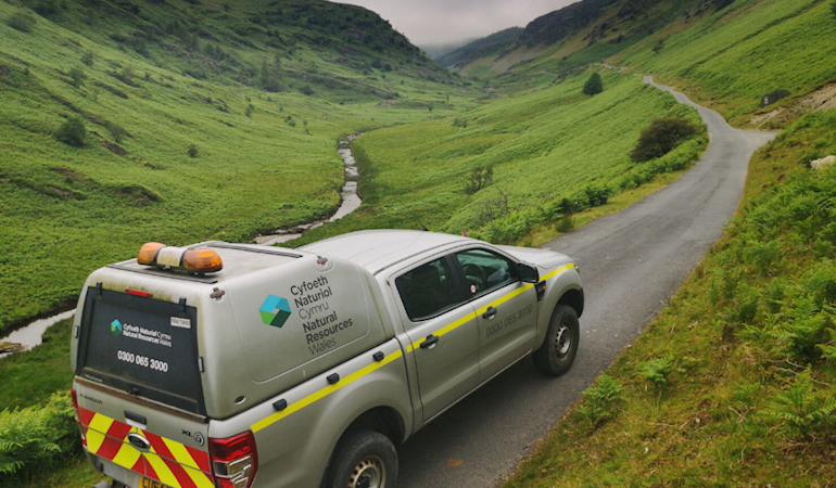 Image of an Natural Resources Wales vehicle on a road in the countryside